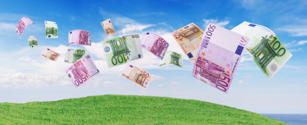 euro notes flying away blue sky as background